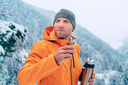 Man with a hot drink cup and a flask dressed bright orange softshell jacket drinking while he trekking winter mountains route. Active people in the nature concept image. 免版税图像