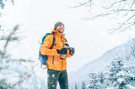 Smiling Man under snowfall dressed bright orange softshell jacket with a hot drink flask while he trekking winter mountains route. Active people in the nature concept image.