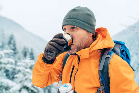 Man drinking a hot drink from flask dressed bright orange softshell jacket while he trekking winter mountains route. Active people in the nature concept image. 免版税图像
