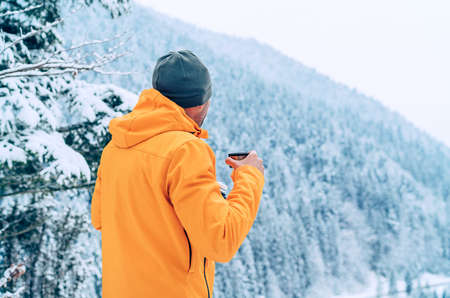 Man with cup drinking a hot drink dressed bright orange softshell jacket and enjoying snowy mountains landscape while he trekking winter route. Active people in the nature concept image.