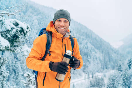 Laughing Man dressed bright orange softshell jacket with a hot drink flask looking at camera while he trekking winter mountains route. Active people in the nature concept image. 免版税图像