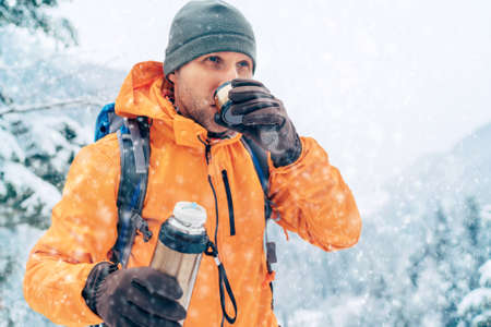 Middle-aged Man with a hot drink cup and a flask dressed bright orange softshell jacket drinking while he trekking winter mountains route. Active people in the nature concept image.