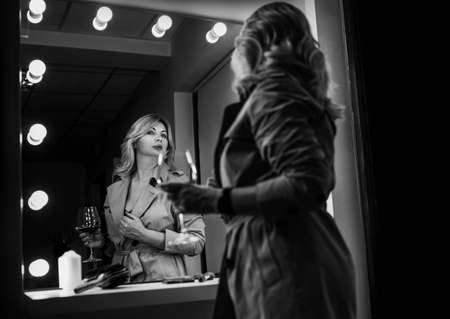 Sensual portrait of middle-aged seductive woman with red wine glass gazing at mirror reflection appreciating her Trench coat outfit. Human emotion or clothing fashion concept black and white image.