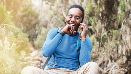 Young African ethnicity man talking via cellphone with somebody and cheerfully laughing as he having a hiking walk in the tropical forest. Happy people, network technology, or traveling concept. 免版税图像