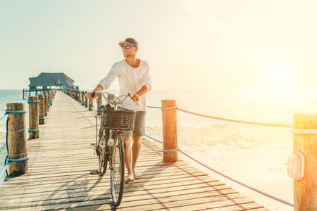 Portrait of a happy smiling barefoot man dressed in light summer clothes and sunglasses riding a bicycle on the wooden sea pier. Careless vacation in tropical countries concept image.