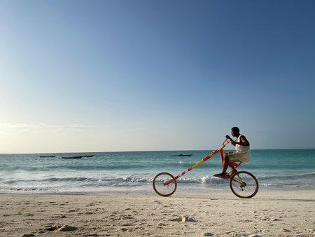 Zanzibar, - Tanzania, January 10, 2021:  Young black man smiling and riding a self maiden funny bright long bicycle with Indian Ocean background in Kiwengwa, Zanzibar, Tanzania.