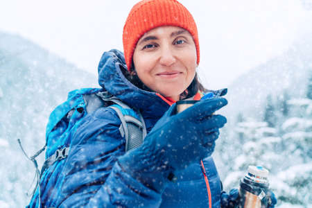 Middle-aged woman smiling, looking at camera drinking a hot drink from flask dressed warm down jacket while she trekking winter mountains route. Active people in the nature concept image.