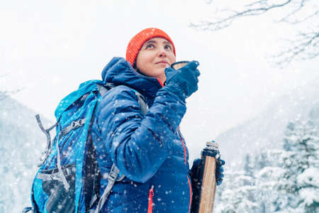 Middle-aged woman smiling and drinking a hot drink from flask dressed warm down jacket while she trekking winter mountains route. Active people in the nature concept image.