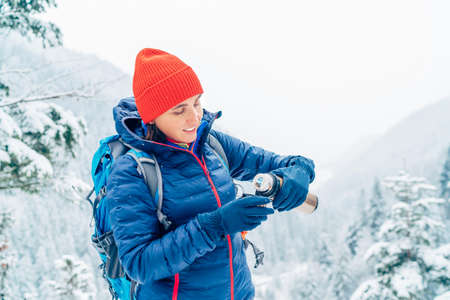 Smiling Woman dressed warm down jacket pouring a hot drink from flask to mug while she has a break on trekking winter mountains route. Active people in the nature concept image.
