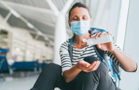 Female traveler with backpack sitting in airport passenger transfer hall in protective face mask applying Hand sanitizer gel. Personal hygiene and traveling in worldwide pandemic time concept image 免版税图像