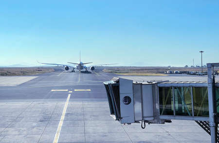 Jet bridge with Aircraft driving by the runway before airplane takeoff. Airways and transportation concept image at Addis Ababa airport, Ethiopia. 免版税图像