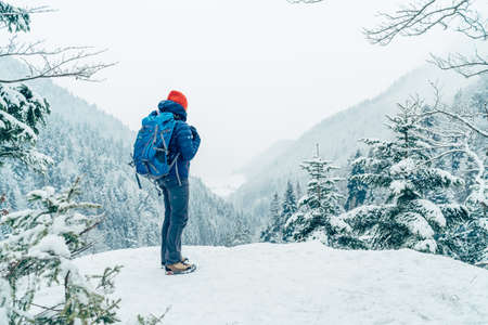 Female backpacker with backpack dressed warm down jacket enjoying snowy mountains landscape while she trekking winter mountain forest route. Active people in the nature concept image. 免版税图像