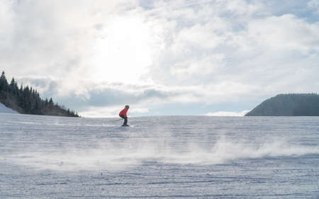 Fast going skier boy ride down the mountain hill. Active winter sport concept image