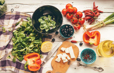 Vegetarian low-calorie Greek salad preparation white wooden table top view. Fresh soft cheese, cherry tomatoes, spinach, paprika, pickled olives chili pepper, paprika, olive oil are there. Standard-Bild