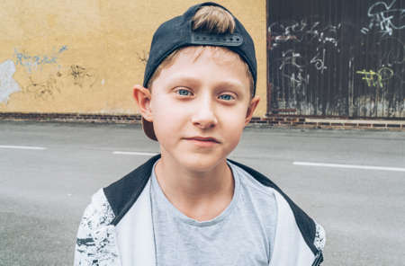 Fashion portrait of caucasian blue-eyed blonde hair 13-year-old skateboarder teenager boy in a baseball cap.  Youth generation Free time spending and an active people concept image.