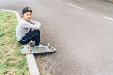 Teenager skateboarder boy with a skateboard sitting on the asphalt road border and resting after he made tricks. Youth generation Freetime spending concept image. 免版税图像