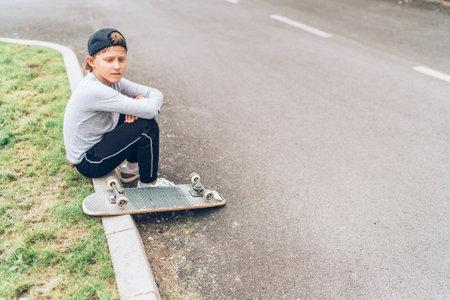 Teenager skateboarder boy with a skateboard sitting on the asphalt road border and resting after he made tricks. Youth generation Freetime spending concept image. Standard-Bild