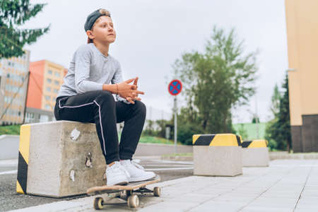 Teenager skateboarder boy portrait in a baseball cap with old skateboard on the city street. Youth generation Free time spending and an active people concept image. Standard-Bild