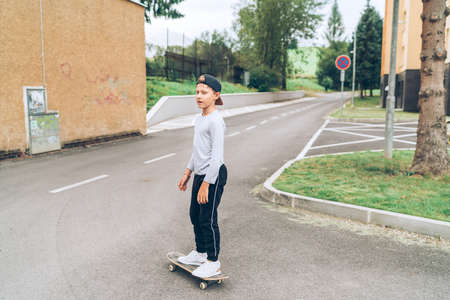 Teenager skateboarder boy in baseball cap riding a skateboard on asphalt street road. Youth generation Freetime spending and active people concept image.