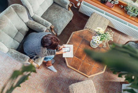 Top view of a female dressed cozy home clothes in comfortable armchair, browsing an internet using smartphone in house sunroom living room. Stay-at-home or business home office concept image