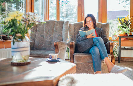 Cheerful smiling female dressed cozy home clothes sitting in comfortable armchair, relaxing, reading a book and drinking morning coffee or tea in house sunroom living room. Stay-at-home concept image 免版税图像