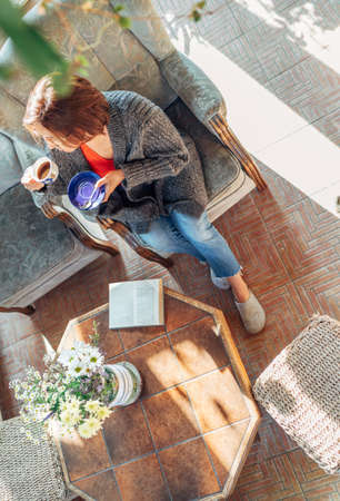 Top view of a female dressed in cozy home clothes sitting in a comfortable armchair and drinking morning coffee in house sunroom living room while she reading a book. Stay home concept image.
