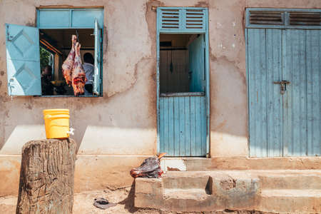 Moshi, - Tanzania, December 28, 2020: The local butcher shop opened a window with beef legs hinged on the hooks. Real local life, traveling or small business concept image in Moshi, Tanzania