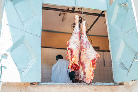 Tanzania, Africa. The local butcher shop opened a window with two beef legs hinged on the hooks. Real local life and traveling concept image.