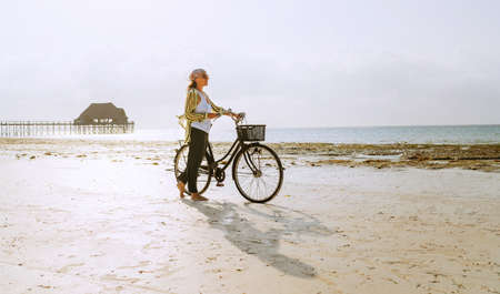 Female dressed light summer clothes have morning walk with old vintage bicycle with front basket on the lonely low tide ocean white sand coast on Kiwengwa beach on Zanzibar island, Tanzania.