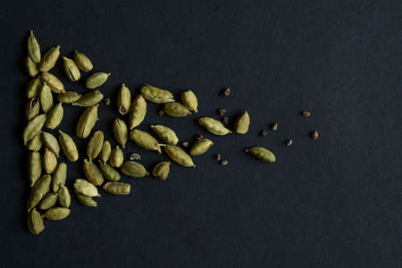 Close up photo of Cardamom pods and seeds pile on the matt black background. It is very popular in Indian and Sri Lanka cuisine.