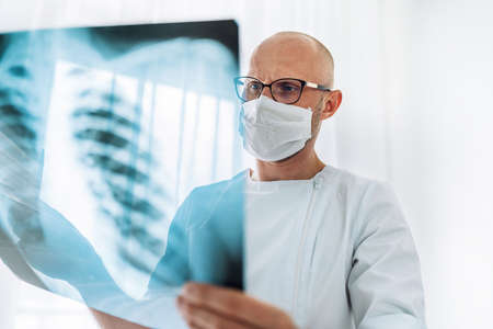 Male doctor in eyeglasses examining the patient chest x-ray film lungs scan at radiology department in hospital.Covid-19 scan body Xray test detection for covid worldwide virus epidemic spread concept Standard-Bild