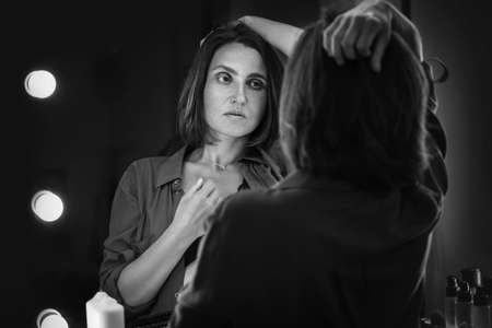 Sensual black and white boudoir portrait of seductive female gazing on her mirror reflection as she ruffling hair. Human emotion or fashion concept image.