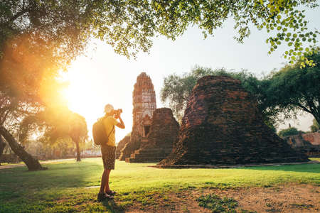 Solo traveler with a backpack taking a photo of ancient Wat Ratchaburana Buddhist temple in holy ancient Ayutthaya city, Thailand Standard-Bild
