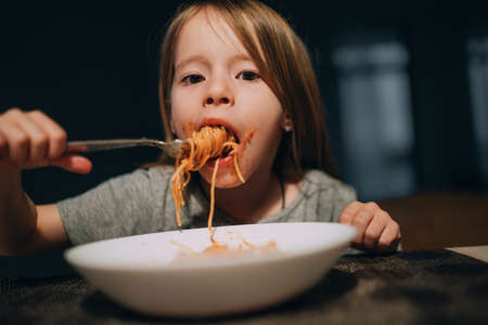 Hungry little girl appetite eating the bolognese pasta reeling up it on the fork and putting to mouth in the low light kitchen table.