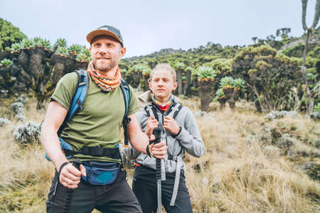 Father and teenage son as Backpackers have hiking walk on the Umbwe route in the forest to Kilimanjaro mountain. Active climbing people and traveling concept.
