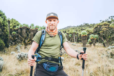 Backpacker man portrait having a hiking walk with trekking poles on the Umbwe route in the forest to Kilimanjaro mountain. Active climbing people and traveling concept.