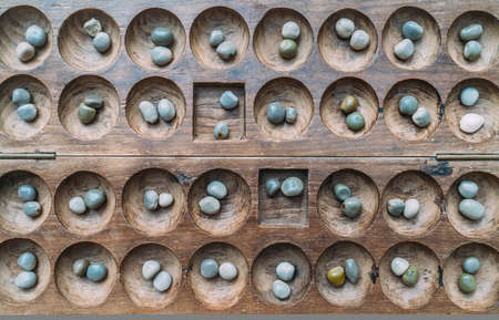 Antique Boa Mancala tradition African Board Game. Vintage Bao carved wooden Board Game. With natural baobab tree seeds Balls.