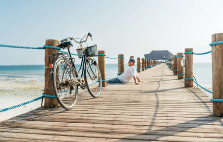 Old bicycle on wooden sea pier and a happy smiling man dressed in light summer clothes sitting and enjoying time on background. Careless vacation in tropical countries concept image. Zanzibar, Tanzani Standard-Bild