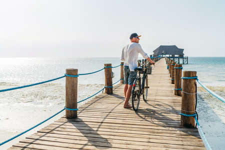 Back view portrait of a man dressed in light summer clothes, sunglasses with old bicycle on the wooden sea pier on the sandy Zanzibar beach.Careless vacation in the tropical countries concept image