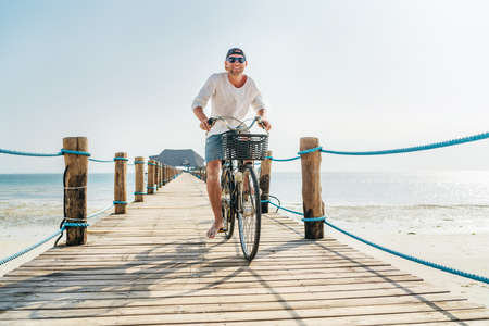 Portrait of a happy smiling man dressed in light summer clothes and sunglasses riding a bicycle on the wooden sea pier. Careless vacation in tropical countries concept image. Kiwengwa beach, Zanzibar