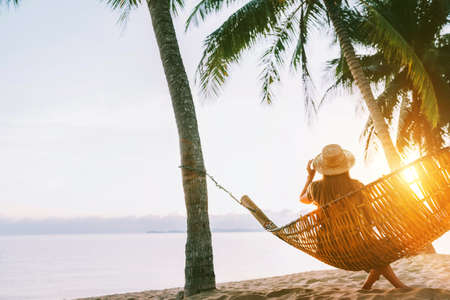 A young woman in straw hat sitting in a hammock swinging between a palm trees on the overseas island sand beach at sunrise time. Koh Samui, Thailand. Exotic vacation concept image. Standard-Bild