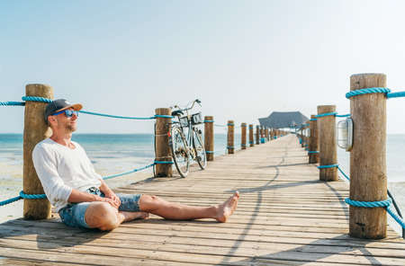 Portrait of a happy smiling man dressed in light summer clothes and sunglasses sitting and enjoying time on wooden sea pier. Careless vacation in tropical countries concept image. Zanzibar,Tanzania