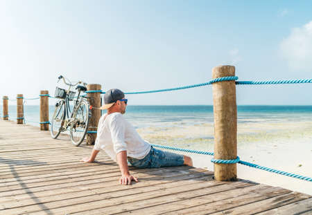 Portrait of relaxing man dressed in light summer clothes and sunglasses sitting and enjoying time and beach view on wooden pier.Careless vacation in tropical countries concept image. Zanzibar,Tanzania