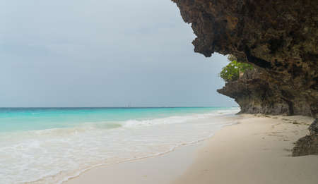 Nungwi rocky sand beach washed with turquoise Indian ocean waves. White sand sandbank beach landscape on Zanzibar island, Tanzania. Exotic countries travel concept