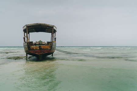 Shallow atoll sandbanks with lonely fisherman boat on low tide Nungwi beach in the Indian Ocean on the Zanzibar island, Tanzania. Exotic countries traveling concept image. Standard-Bild