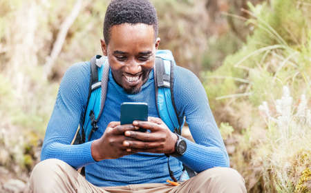 Young African ethnicity man video chatting via cellphone with somebody and cheerfully laughing as he having a hiking walk in the forest. Happy people, network technology, or traveling concept Standard-Bild