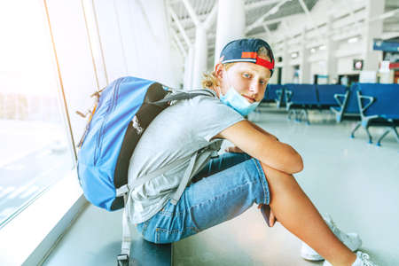 Portrait of lonely teen solo traveler with a backpack in empty airport passenger transfer hall in protective face mask and sadly looking at camera. Traveling in worldwide pandemic time concept image