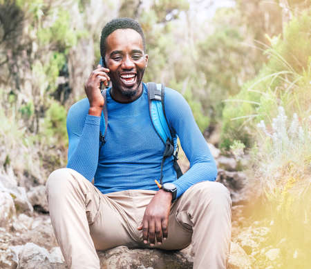 Young African ethnicity man talking via cellphone with somebody and cheerfully laughing as he having a hiking walk in the tropical forest. Happy people, network technology, or traveling concept. Standard-Bild
