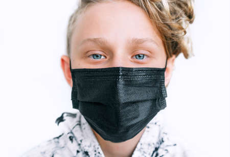 Portrait of blue-eyed teen boy using a black facial mask during a COVID-19 world pandemic looking at the camera. Self-protection and stop virus spreading measures concept image