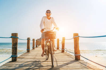 Portrait of a happy smiling man dressed in light summer clothes and sunglasses riding a bicycle on the wooden sea pier. Careless vacation in tropical countries concept image. Standard-Bild
